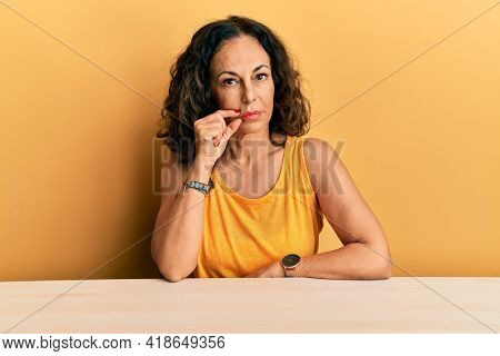 Beautiful middle age woman wearing casual clothes sitting on the table mouth and lips shut as zip with fingers. secret and silent, taboo talking