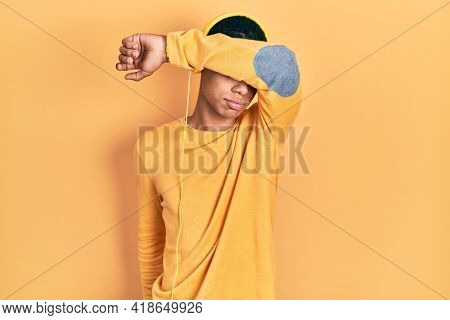 Young african american guy listening to music using headphones covering eyes with arm, looking serious and sad. sightless, hiding and rejection concept