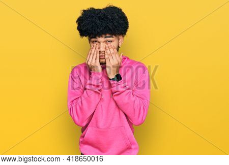 Young african american man with afro hair wearing casual pink sweatshirt rubbing eyes for fatigue and headache, sleepy and tired expression. vision problem