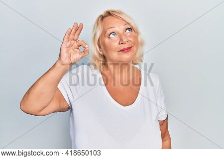 Middle age blonde woman doing ok positive gesture smiling looking to the side and staring away thinking.