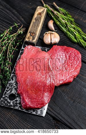 Raw Marble Beef Meat Fillet Steak On Butcher Cleaver. Black Wooden Background. Top View