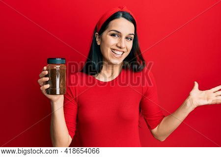 Young hispanic woman holding soluble coffee celebrating achievement with happy smile and winner expression with raised hand