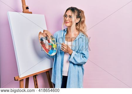 Beautiful young blonde woman standing drawing with palette by painter easel stand smiling looking to the side and staring away thinking.