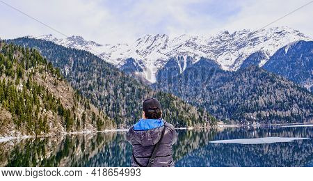 A Man In A Black Jacket With A Blue Hood Takes A Picture Of A Beautiful Winter Landscape Of The Cauc