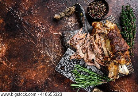 Roasted And Cut German Pork Knuckle Eisbein Meat On A Wooden Board With Meat Cleaver. Dark Backgroun