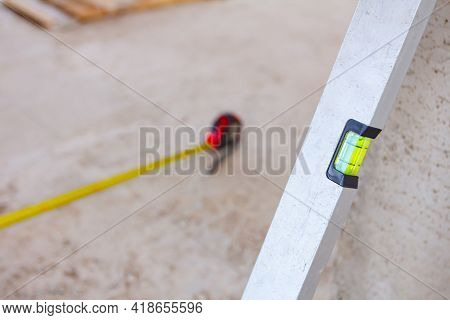 Spirit Level Placed Next To The Wall And Metal Measure Tape Is On The Concrete Floor After Usage For