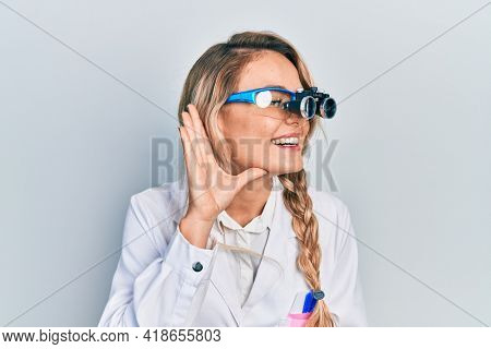 Beautiful young blonde woman wearing optometry glasses smiling with hand over ear listening and hearing to rumor or gossip. deafness concept.
