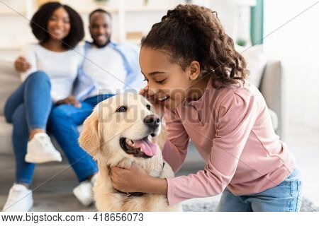 Young Black Girl Hugging With Dog And Whispering Secret