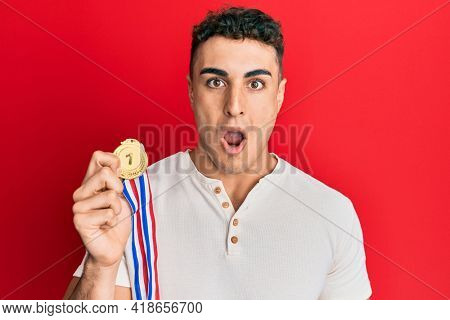 Hispanic young man holding first place medal scared and amazed with open mouth for surprise, disbelief face