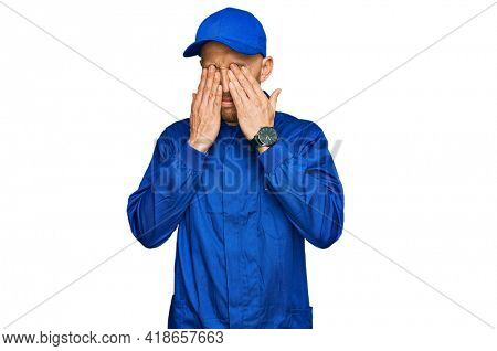 Bald man with beard wearing builder jumpsuit uniform rubbing eyes for fatigue and headache, sleepy and tired expression. vision problem