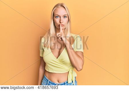 Young blonde girl wearing casual clothes asking to be quiet with finger on lips. silence and secret concept.