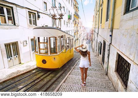Woman Tourist Walking In Narrow Streets Of Lisbon City Old Town. Famous Retro Yellow Funicular Tram