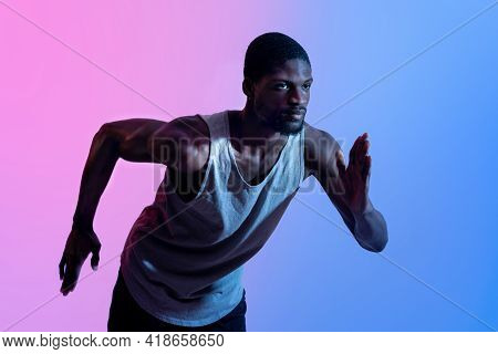 Portrait Of Young Black Sprinter Running In Neon Light. Professional Sports Concept