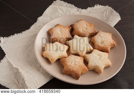 Delicious Homemade Cookies In The Shape Of Stars Sprinkled With Sugar. Laid Out On A Plate On A Dark