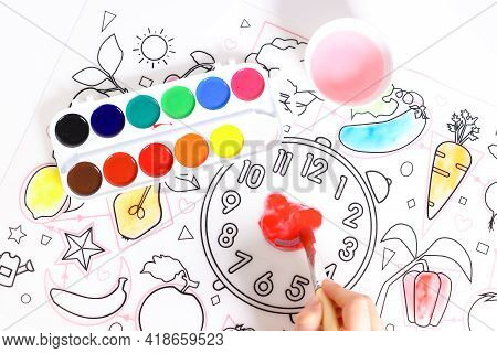 A Child Draws With Paints On A Drawing Mat. Picture On A White Background Only The Child's Hands Are