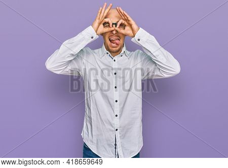 Bald man with beard wearing business shirt and glasses doing ok gesture like binoculars sticking tongue out, eyes looking through fingers. crazy expression.