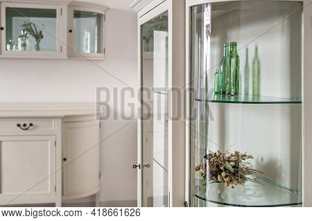 White Old Style Cabinets With Glass Shelves In A Classic Style Apartment. Green Glass Bottles And Dr