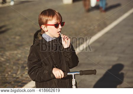 Boy Enjoying With Scooter On A Walk At Sunny Day. Active Leisure, Lifestyle And Fashion Concept. Boy
