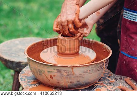 Father And Son Making Ceramic Pot. Family Working On Pottery Wheel. Potters And Child Hands. Pottery