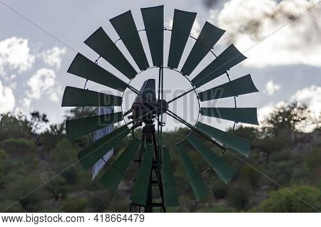 Blades Of  Wind Engine Lifting Water From Well For Watering Wild Animals. The Profile Of  Windmill I