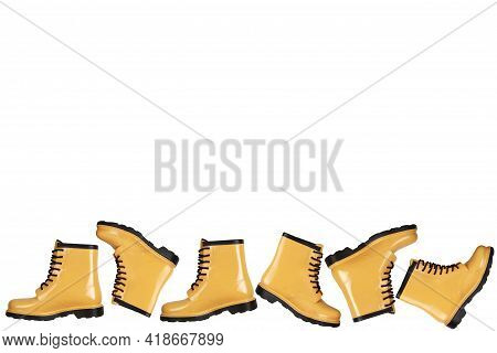 Creative Background With Yellow Rubber Boots On White Background.lots Of Women's Rubber Boots.autumn