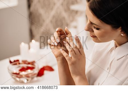 Female Hands Applying Transparent Nail Polish On Healthy Natural Woman's Nails In Beauty Salon. Mani