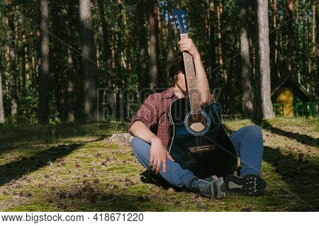 Portrait Of A Shy Guy Sitting In The Forest, Covering His Face With A Guitar. Against The Background