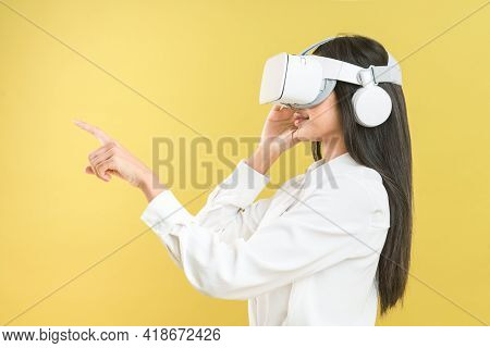 Asian Woman Wearing Vr Headset Over Yellow Background To Get Excite Experience Of Virtual Reality Te