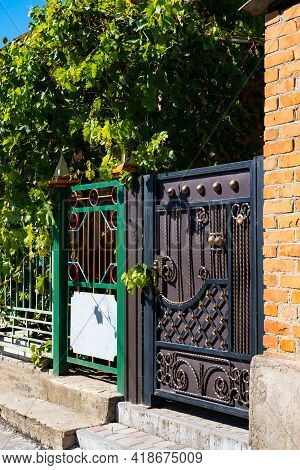 Wooden Gate With Wrought Iron Elements Near A Residential Building.