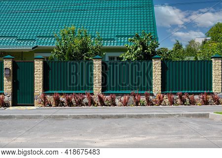 Green Metal Corrugated Fence With Brick Pillars On The Background Of A Beautiful House.