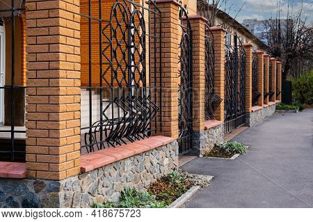 Modern, High, Beautiful Fence With Steel Rods And Pillars Of Brick.