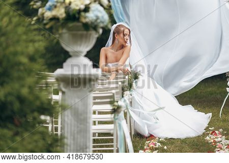 Beautiful Bride In A Magnificent Wedding Dress Posing Among Greenery On The Street. Girl Poses In A
