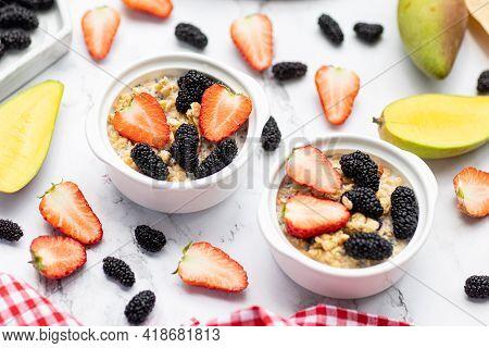 Breakfast Oatmeal Porridge With Fresh Fruits And Berries, Chia Seeds On White Marble Background. Oat
