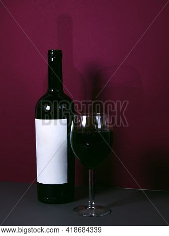 A Glass Of Red Wine On A Red Background With A Wine Bottle In The Background. Stylish Advertising Of