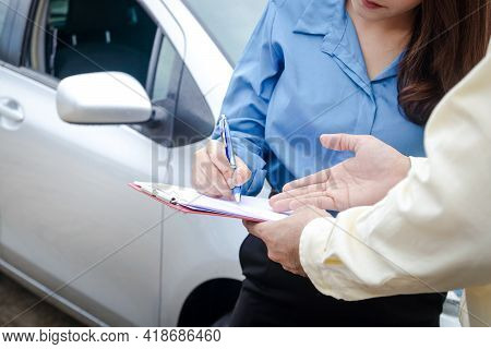 A Woman Driving A Car Has An Accident During The Rain. Signing The Auto Insurance Claim Document Wit