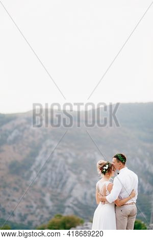 The Groom And The Bride In Wreaths Stand On The Top Of The Mountain Embracing, The Groom Kisses The