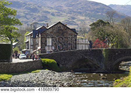 Beddgelert Village - Wales - 24 April 2021 : Landscape View Of A Traditional Old Stone Bridge Across