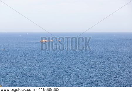Small Island In The Mediterranean Sea With A Lighthouse And Small Boats In The Sea