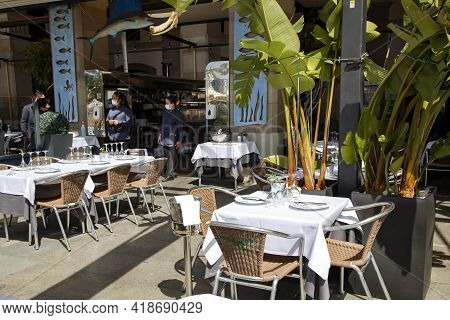 Spain, Barcelona, March, 2021: Served Tables With A White Tablecloth Awaiting Visitors On The Open T