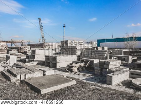 A Machine Crane At A Construction Site With A Bunch Of Concrete Structures. Concrete Materials In An