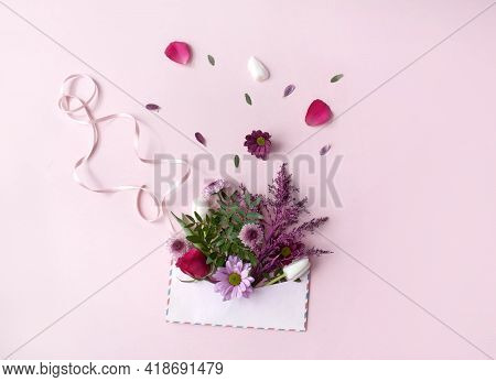 Assorted Flowers Falling Out Of An Envelope With Gift Ribbon