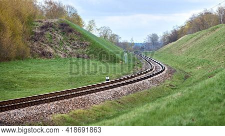 Selective Focus Railway Track Twists And Turns Between Hills. Empty Rounding And Turning Single Trac