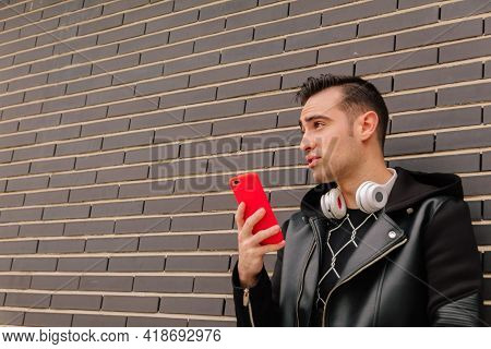 A Young Hispanic Man Talking On His Smartphone, On A Street Outdoors. Lifestyle Concept.