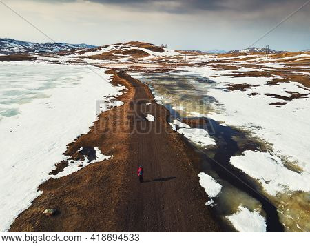 Melting Snow On The Lake And Mountains In Early Spring. Aerial Drone View. Tourist Walks Along The R