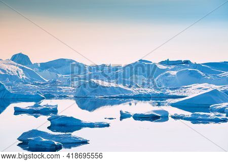 Iceberg In The Ilulissat Icefjord, West Coast Of Greenland. Calm Water With Reflections Of Icebergs