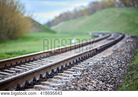 Selective Focus Railway Track Turns And Twists Between Hills. Empty Rounding And Turning Single Trac