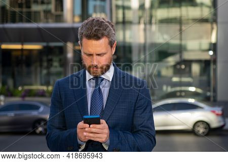Portrait Of Businessman Standing In A Office. Businessman Talking On Phone. Portrait Of Cheerful Bus