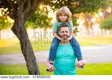 Dad And Child Having Fun Outdoors. Father Giving Son Ride On Back In Park. Portrait Of Happy Father