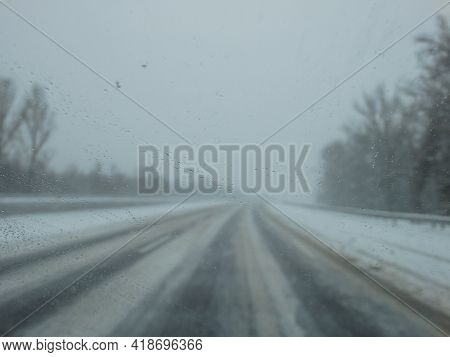 Driving In A Snow Storm. Poor Visibility Through The Driver's Glass Onto The Road Covered With Snow