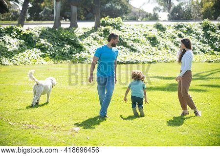 Happy Child And Parents With Dog As Family Running In The Nature. Young Family With Child Having Fun